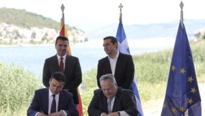 Greek Prime Minister Alexis Tsipras, background right, and his Macedonian counterpart Zoran Zaev, background left, look on as Greek Foreign Minister Nikos Kotzias, right, and his Macedonian counterpart Nikola Dimitrov sign an agreement on Macedonia's new name in the village of Psarades, Prespes Greece, on Sunday, June 17, 2018. The preliminary deal launches a long process that will last several months. If successful, it will end a decades-long dispute between neighbors Greece and Macedonia _ which will be renamed North Macedonia. (AP Photo/Yorgos Karahalis)